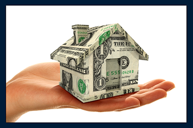 persons hand holding a house made of dollar bills